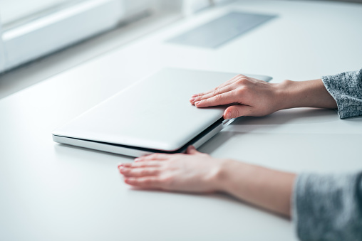 Businesswoman's hands closing or opening laptop on white table in bright office. 1175740158