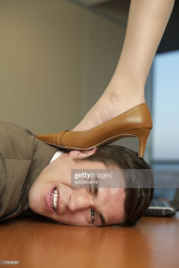 Businesswoman's high heeled shoe on businessman's head : Stock Photo