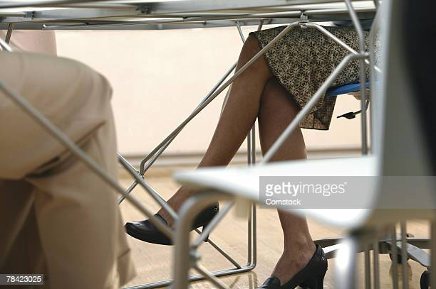 Businesswoman's legs under table during meeting
