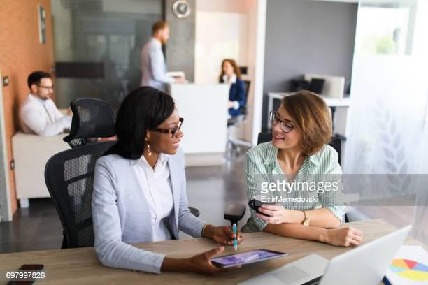 Businesswomen analyzing bar graph using digital tablet