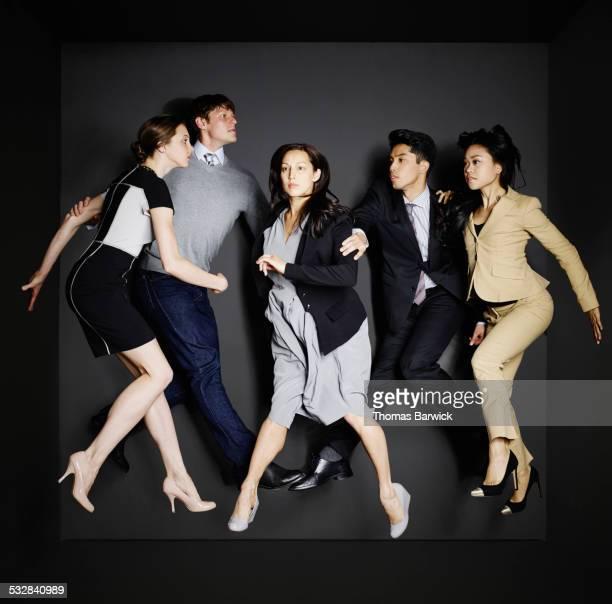 Businesswomen and businessmen walking in mid air