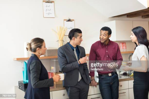 businesswomen and men having informal meeting in office kitchen - heshphoto stock pictures, royalty-free photos & images