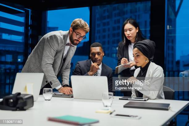 businesswomen and men looking at laptop during conference table meeting - abbigliamento da lavoro formale foto e immagini stock