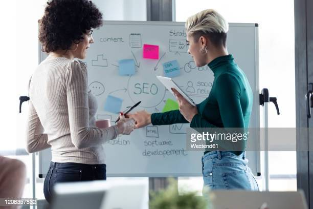 businesswomen at a flipchart, presenting ideas for a search engine optimisation - search engine stock pictures, royalty-free photos & images