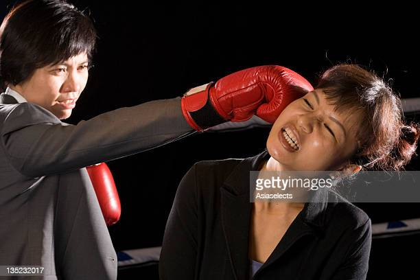 Businesswomen being hit by her opponent in a boxing ring