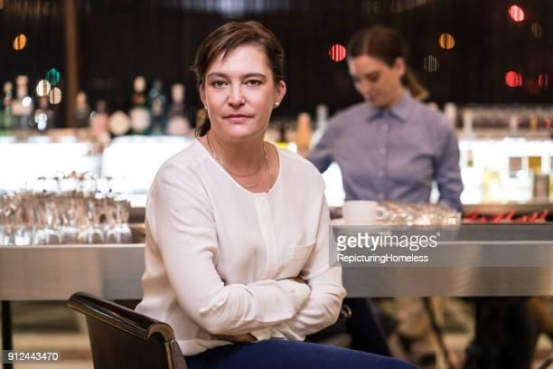 Eine Geschäftsfrau sitzt mit verschränkten Armen in einer Bar und schaut in die Kamera
