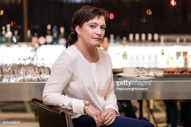 Eine Geschäftsfrau in einer Bar und lehnt an einem Stuhl