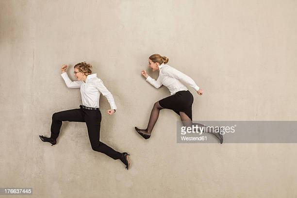 businesswomen chasing against beige background - beige background stock pictures, royalty-free photos & images
