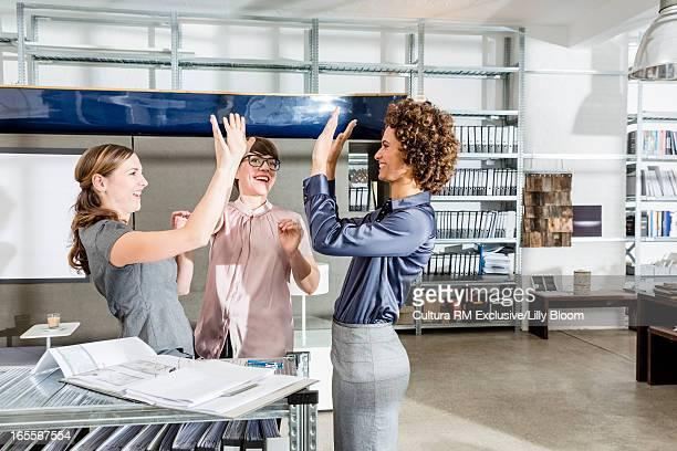 Businesswomen cheering in office