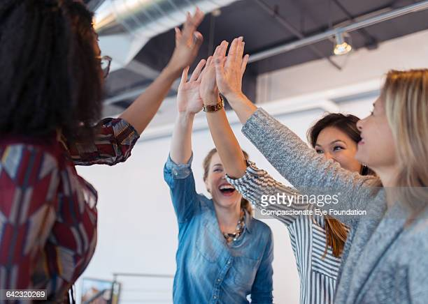 businesswomen cheering in office - high five stock-fotos und bilder