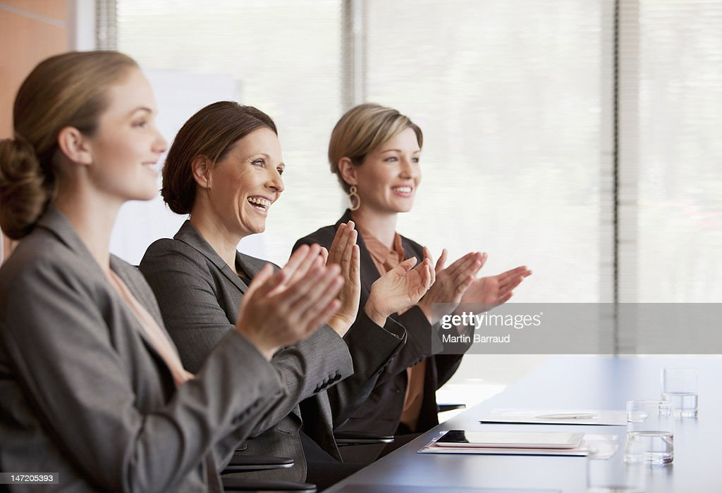 Businesswomen clapping in conference room : Stock Photo