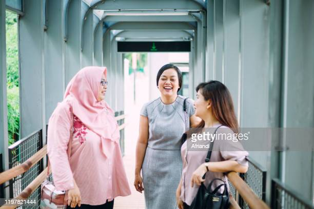 businesswomen conversing after meeting up in the pedestrian bridge - indonesia stock pictures, royalty-free photos & images