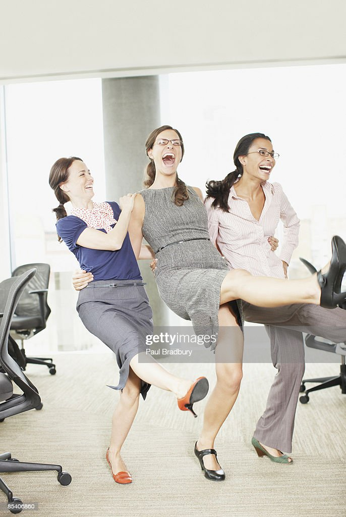 Businesswomen dancing in office : Stock Photo