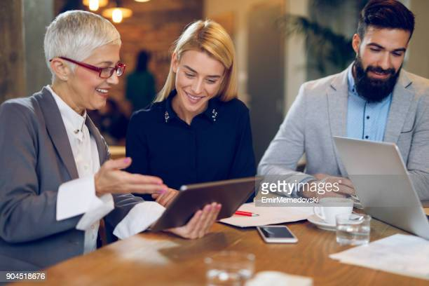 Mujeres empresarias hablar de negocios durante la reunión mientras que uso de tableta digital