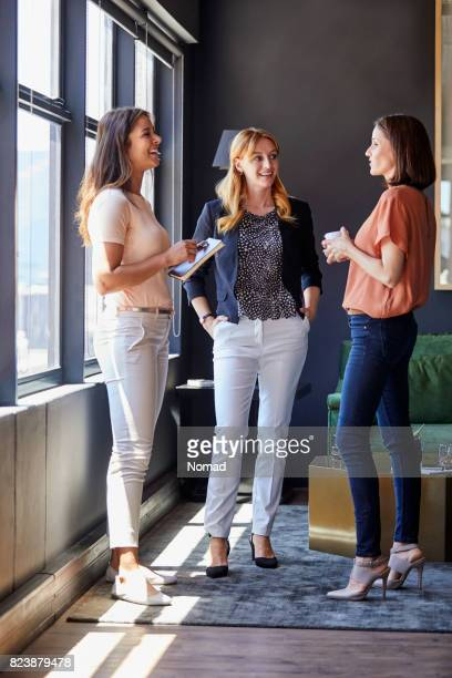businesswomen discussing by window in office - tre persone foto e immagini stock