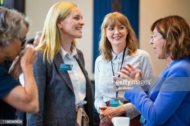 businesswomen discussing during coffee break in seminar - unterhaltungsveranstaltung stock-fotos und bilder