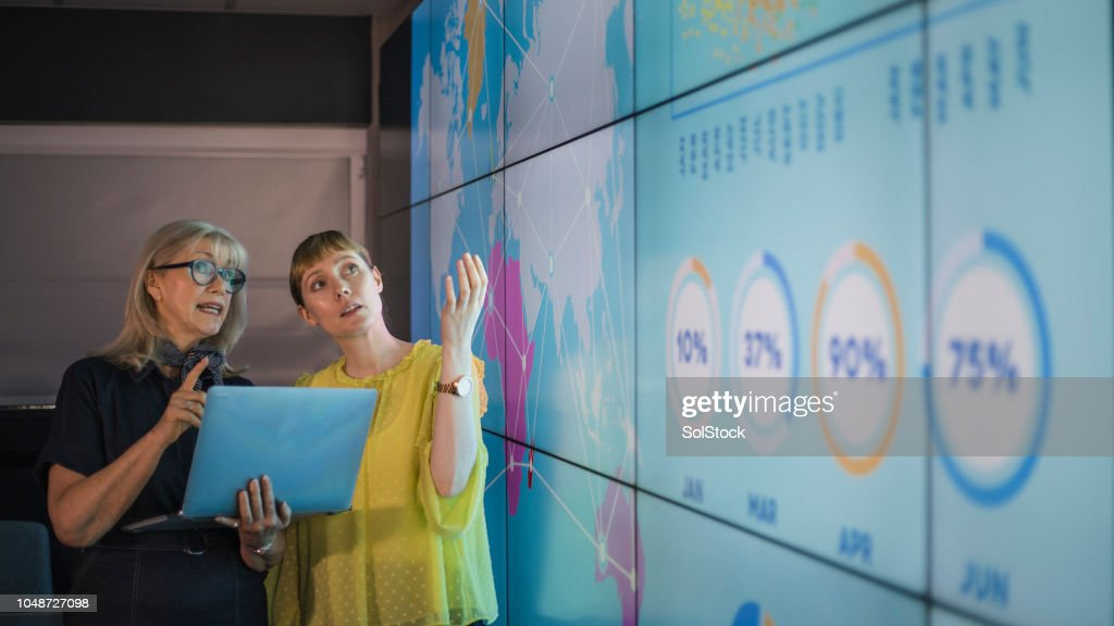 Businesswomen Discussing Ideas Against an Information Wall : Foto stock