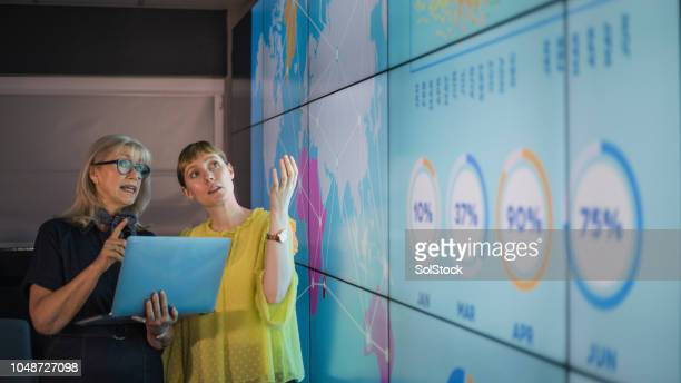businesswomen discussing ideas against an information wall - ricerca foto e immagini stock