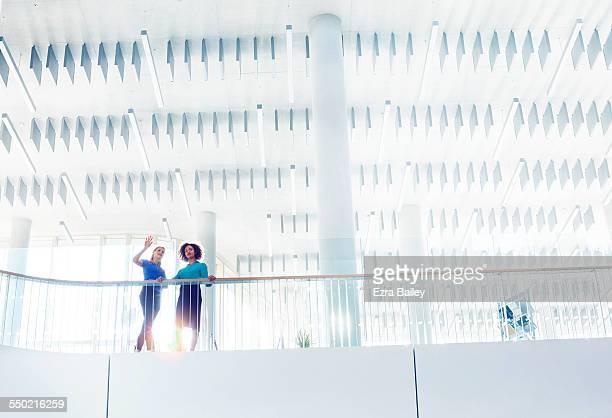 Businesswomen discussing ideas in open plan office