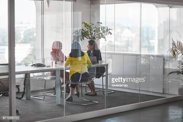businesswomen discussing in meeting at board room - glass stock photos and pictures
