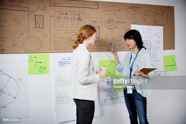 Businesswomen discussing over charts while standing in office