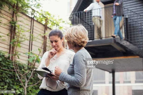 Businesswomen discussing over digital tablet at office yard