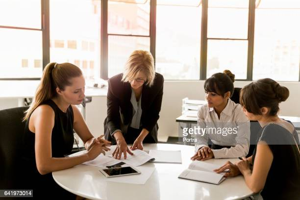 Businesswomen discussing over documents at table