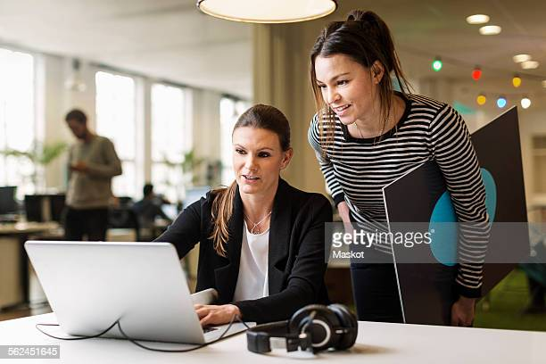 Businesswomen discussing over laptop in creative office