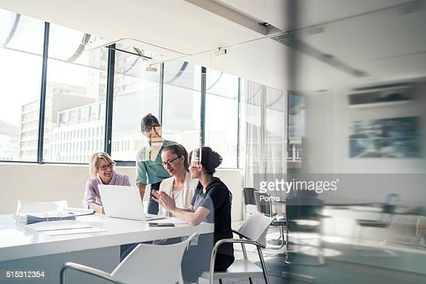 businesswomen discussing over laptop in office - brightly lit stock pictures, royalty-free photos & images
