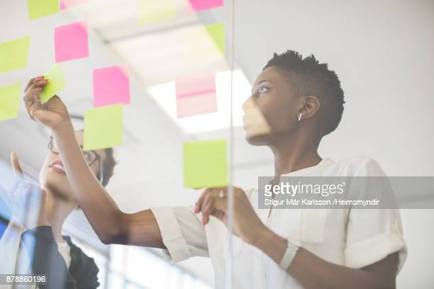 businesswomen discussing over sticky notes - to do list stock pictures, royalty-free photos & images