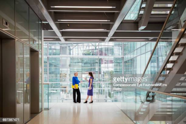 Businesswomen discussing plans in office hallway