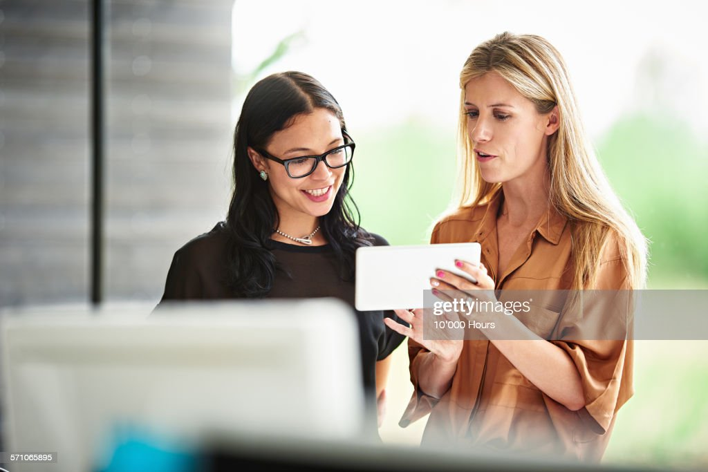 Businesswomen discussing plans on a digital tablet : Stock Photo