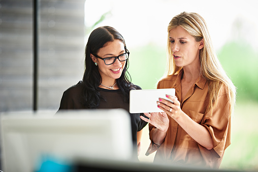 Businesswomen discussing plans on a digital tablet - gettyimageskorea