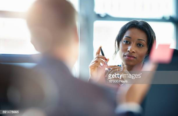 businesswomen discussing plans with a colleague - differential focus stock pictures, royalty-free photos & images