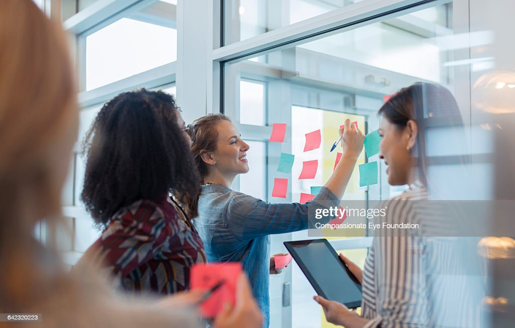Businesswomen discussing project in office : Stock Photo