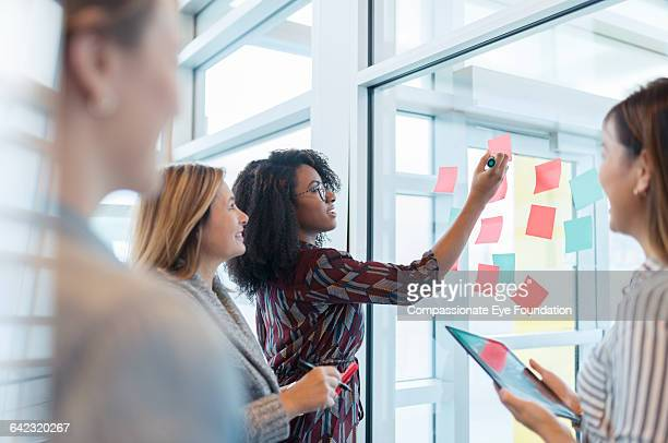 businesswomen discussing project in office - compassionate eye foundation stock pictures, royalty-free photos & images
