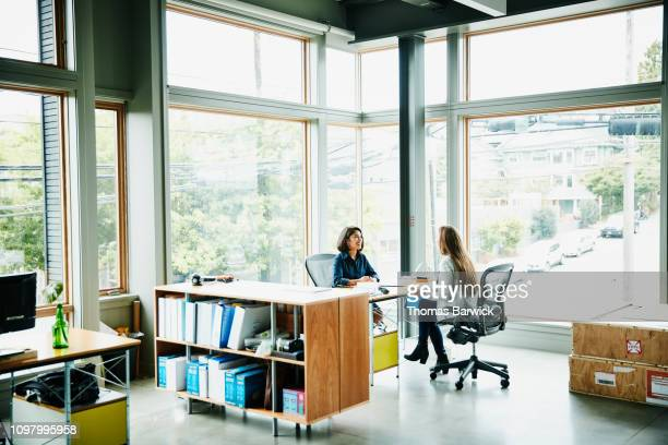 businesswomen discussing project while seated at office workstation - bedrijven financiën en industrie stockfoto's en -beelden