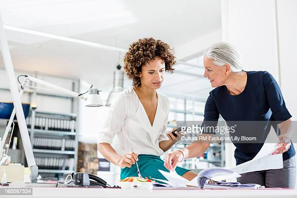 Businesswomen eating and working