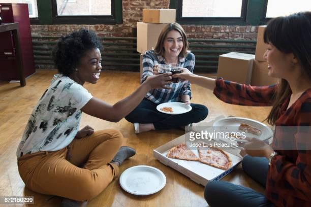 businesswomen eating pizza and toasting on floor of new office - besonderes lebensereignis stock-fotos und bilder