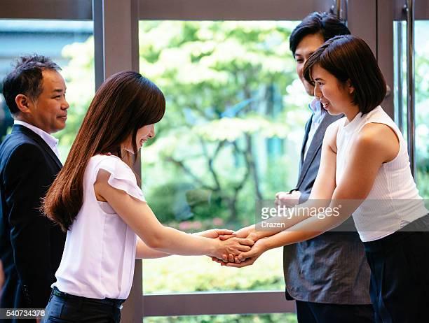 名刺を手渡す 実業 と握手