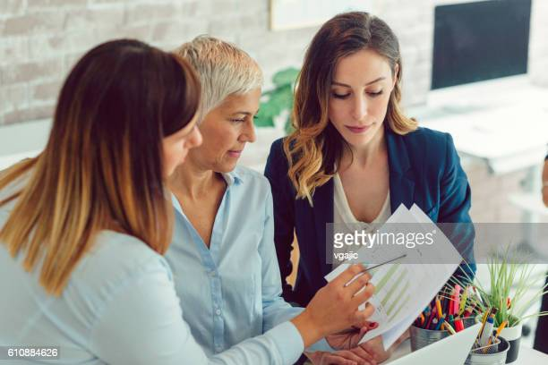 Businesswomen Expertise Charts In Their Office.