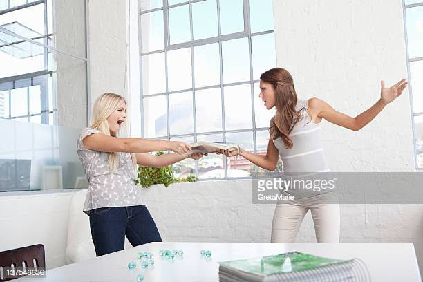 Businesswomen fighting over papers