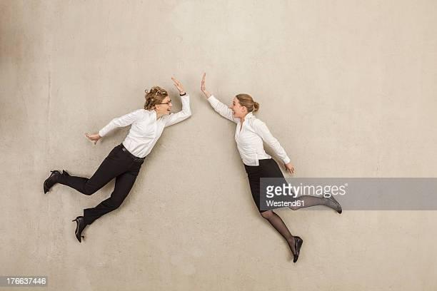 Businesswomen giving high five against beige background