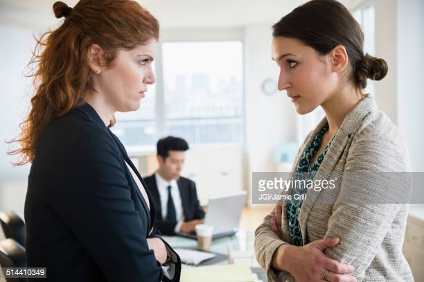 businesswomen glaring at each other in office - rivaliteit stockfoto's en -beelden