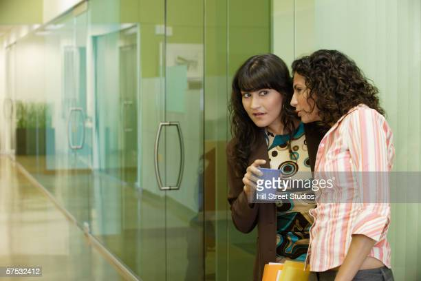 Businesswomen gossiping in office hallway