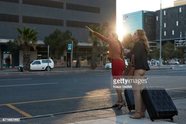 Businesswomen hailing a cab, at sunset