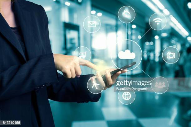 Businesswomen hand using cellphone omni-channel shopping ctr with hi tech icon flow on blur abstract background shopping mall department store