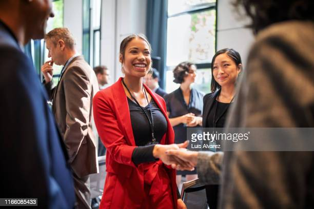 businesswomen handshaking in auditorium corridor - bijwonen stockfoto's en -beelden