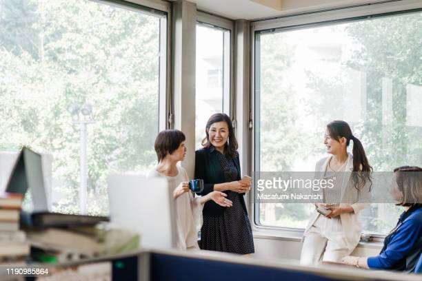 businesswomen having a casual meeting by the window - 従業員エンゲージメント ストックフォトと画像