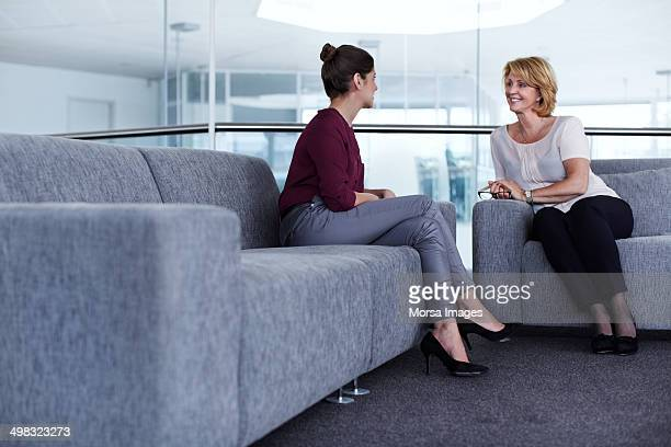 businesswomen having casual discussion - red pants stock pictures, royalty-free photos & images